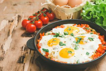 Tasty and Healthy Shakshuka in a Frying Pan. Fried eggs with tomatoes, bell pepper, vegetables and herbs. Middle eastern traditional dish.