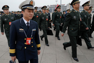 Military delegates arrive to the third plenary session of the National People's Congress (NPC) at the Great Hall of the People to take a part in a vote on a constitutional amendment lifting presidential term limits, in Beijing