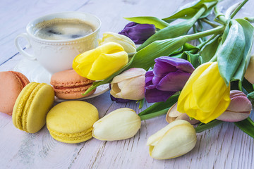 Coffee break with french macaroons and multicolored tulips