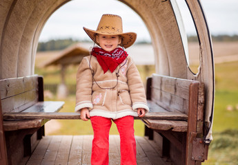 little girl in cowboy hat sits in old cart