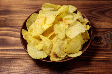Plate of potato chips on wooden table