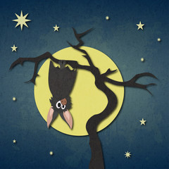 Bat hanging on a dry tree on background of full moon and starry night.