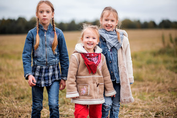 three girls, sisters, girlfriends in the field in the cold season