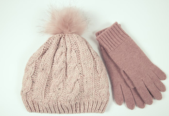 Wool hat and gloves for winter weather on a white background.
