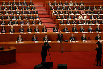 Chinese President Xi Jinping and other top officials clap their hands after a vote of the National People's Congress (NPC) at the Great Hall of the People in Beijing
