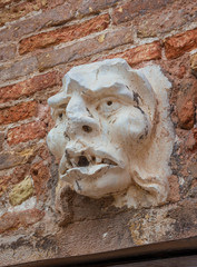 Frightening demon face old relief on wall in Venice