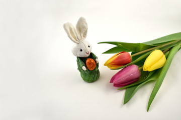 Colorful tulips with Easter bunny stock images. Easter decoration on a white background. Spring decoration images. Bouquet of colorful tulips. Easter Bunny with tulips