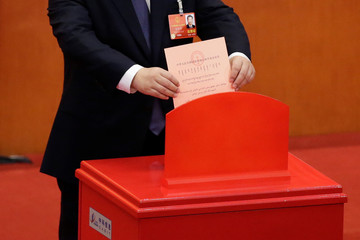 Chinese President Xi Jinping drops his ballot during a vote on a constitutional amendment lifting presidential term limits, at the third plenary session of the National People's Congress (NPC) at the Great Hall of the People in Beijing