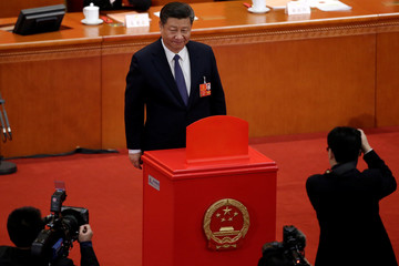 Chinese President Xi Jinping pauses after casting his ballot during a vote on a constitutional amendment lifting presidential term limits, at the third plenary session of the National People's Congress (NPC) at the Great Hall of the People in Beijing