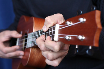 close up ukulele in musician hands, left hand view