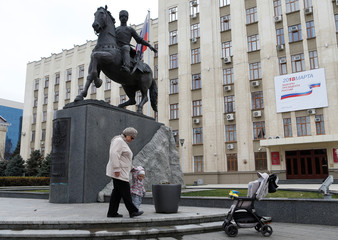 A woman walks with a child near a monument of Kuban Cossacks in front of the Krasnodar regional administration headquarters with a board, which informs of the upcoming presidential election, in Krasnodar