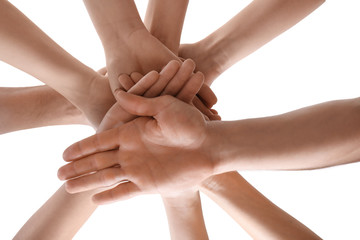 Young people putting hands together as symbol of unity, on white background