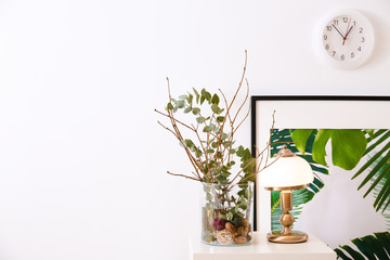 Elegant lamp and glass vase with branches on table indoors