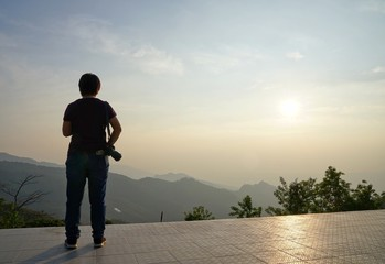 Photographer holding camera looking at the view of beautiful mountains during sunset at  Doi Pha Tang, Chiangrai, Thailand