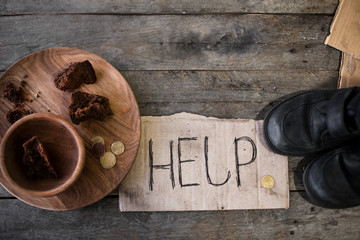 Piece of cardboard with word HELP, old shoes and bread on wooden background