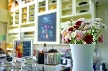White ceramic vase of mixed colorful fresh flowers decorated in coffee shop