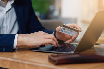 Man holding in hand a credit card and using laptop for online shopping. Web banking and international network payment. Online payment concept.