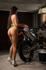 Sexy young model washing motorcycle