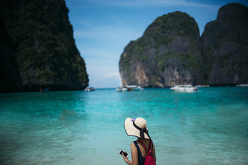 Woman with smartphone and hat on the beach in Thailand
