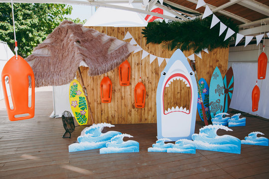 Beautiful scenery and design of a child's birthday party in a marine style with surfers, sharks, waves, garlands in the open air under the awning. Organization and decoration of family holidays