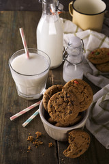 Chocolate chip cookies and milk on a rustic wood background,