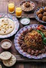 Mejadra with hummus, kashke bademjan and pitas, wooden background