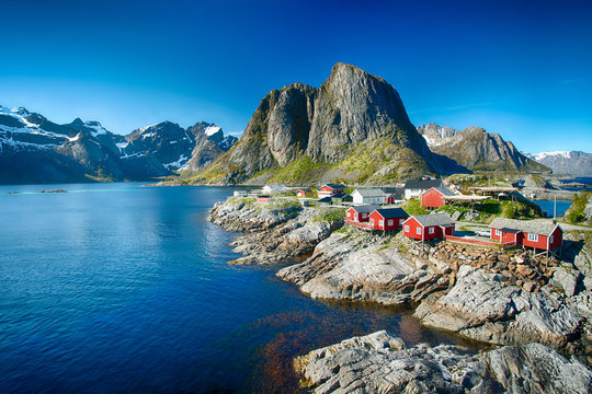 The village of Reine under a sunny, blue sky, with the typical red rorbu houses.