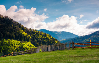 lovely rural landscape in Carpathians. wooden fence along the grassy hillside