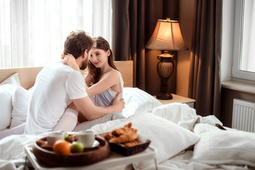 Passionate male and female embrace each other, look with love, spend their honeymoon in luxury hotel, enjoy delicious breakfast. Affectionate young couple in cozy bedroom enjoy togetherness