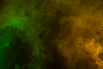 Green and yellow smoke texture on a black background. Texture and abstract art