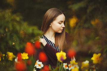 beautiful girl sits at the planted flowers.