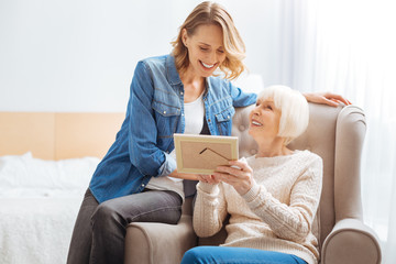 Pleasant memories. Cheerful senior woman feeling happy while sitting in a soft cozy armchair and showing a nice old photo to her kind attentive granddaughter and smiling
