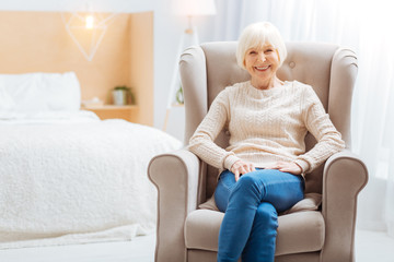 Comfort. Cute pleasant aged lady feeling good while being alone in a beautiful light room and sitting in a soft comfortable armchair