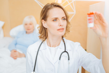 Careful doctor. Skilled professional experienced doctor feeling confident while standing next to her aged ill patient and looking at the little box with necessary pills