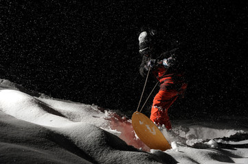 Snowboarder riding on board at night under the snow