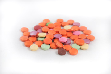 Multicolored round tablets closeup on white background