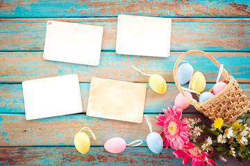 Wall Mural - Colorful Easter eggs in nest with flower and empty old paper photo album on wood table  - concept of remembrance and nostalgia holiday in spring. vintage style