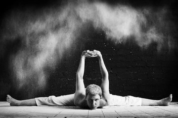 A man doing yoga in a white cloud of dust in a dark room. The concept of energy. Black-and-white photo.
