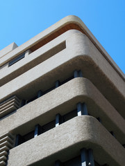 corner of a brutalist concrete concrete tower block with textured rounded corners against a blue sky