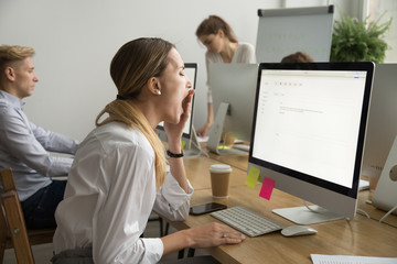 Tired businesswoman yawning working on computer sitting at desk with colleagues, sleepy employee gaping suffering from lack of sleep, feeling bored or chronic fatigue in office concept, side view