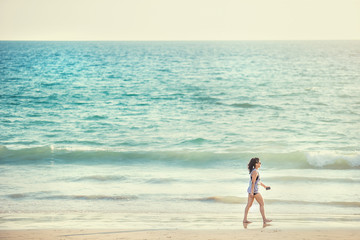 Fototapete - Woman walk on an empty wild beach