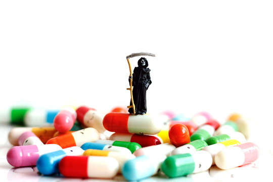 Miniature people: Demon of death standing on drugs. Medical health and against drugs concept.