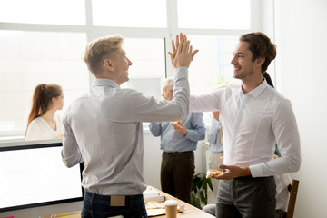 Smiling male coworkers giving high five eating pizza together at office break, happy young men colleagues slapping hands celebrating success achievement at staff party, teammates friendship concept