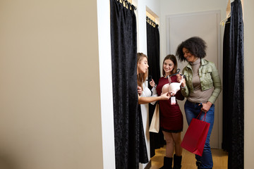 Beautiful young woman asking for a friends opinion in the fitting room of lingerie store. Female tries on bra in underwear shop. Shop assistant helps girl to choose right size in changing room.