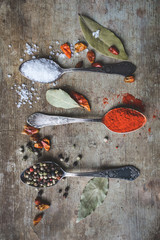 Top view of colorful spices in vintage spoons and dried chilly and bay leaves on old rustic background. Vintage toned. Spices background