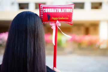 Young female university graduate holding certificate and congratulations gifts stands in front university building in commencement ceremony day.