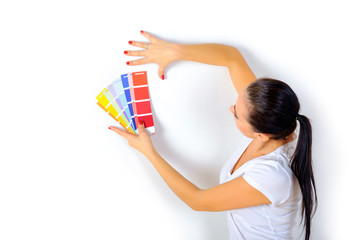 girl painter chooses the color of paint to repair the room