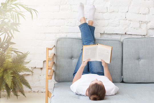 Young woman laying on couch in loft interior, reading interesting old paper book