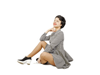 Cute young girl in plaid dress doing clown pose. Isolated. White background.