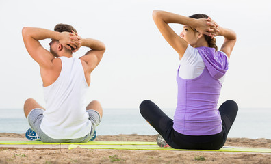 Cross-legged couple practice yoga on beach in morning